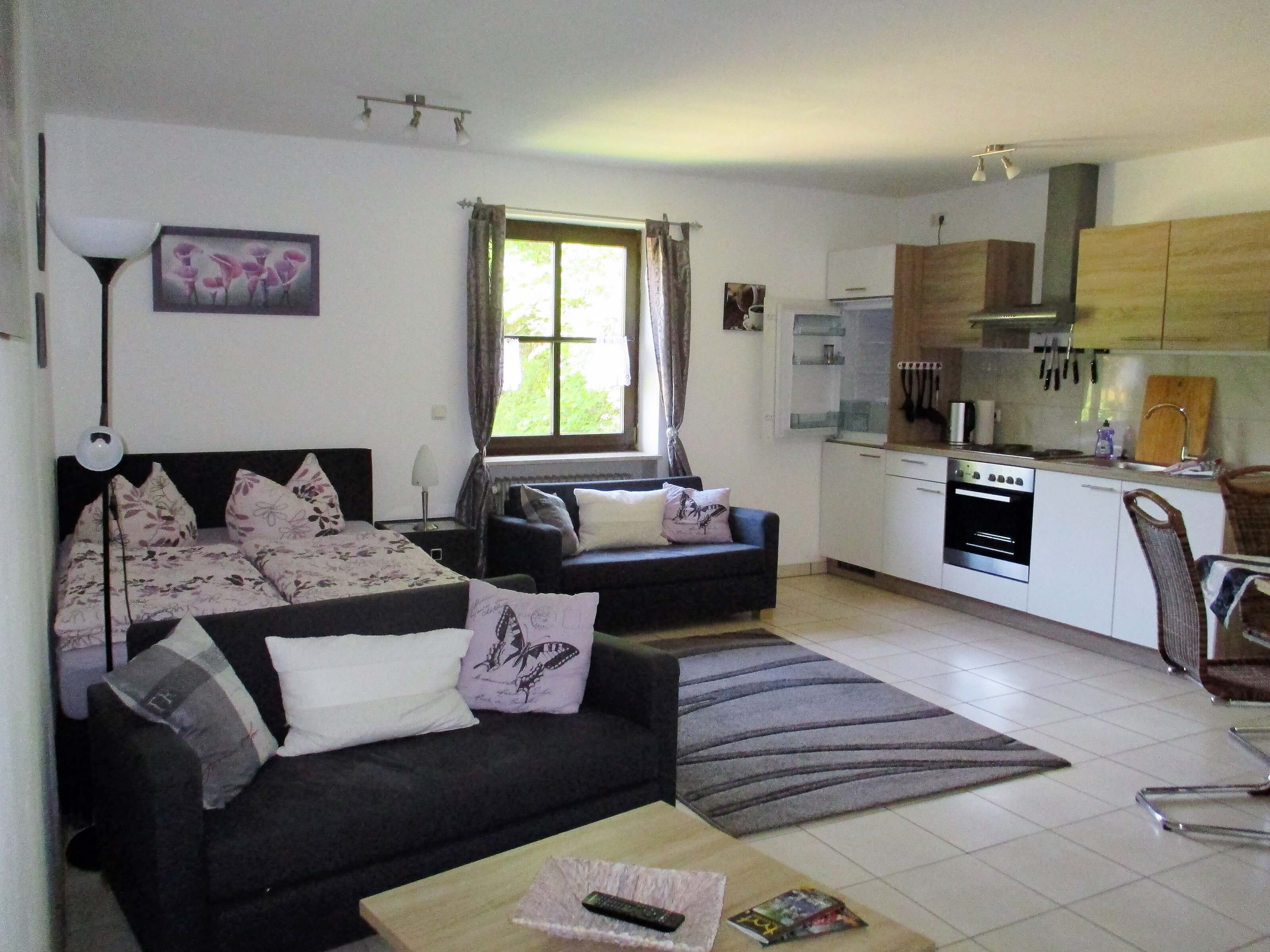 Wohnzimmer mit Bett und Küche – Reiterhof Finkenmühle